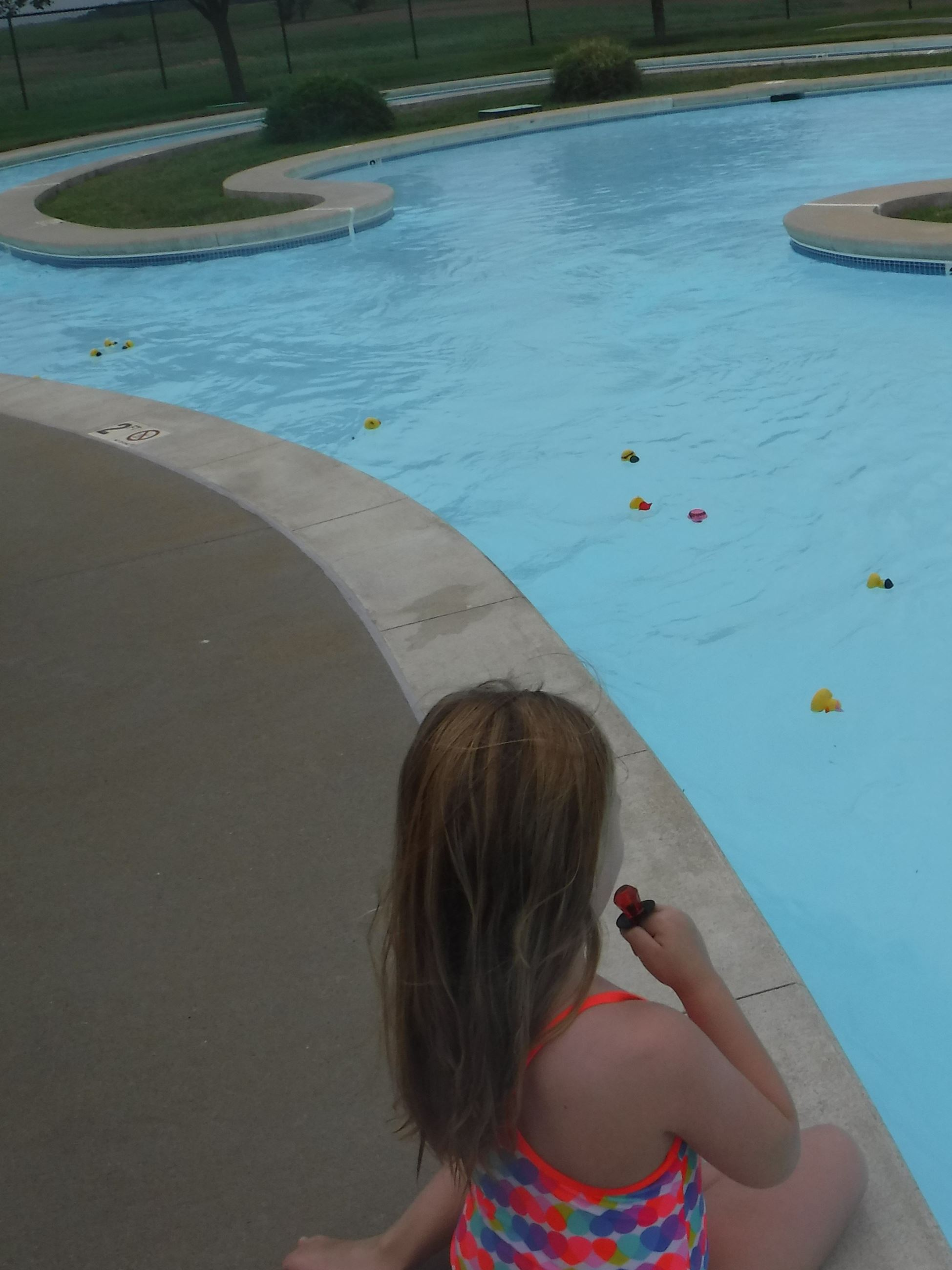 Child watching the ducks race around the curve in the lazy river at JAC.